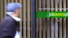 Man walks part a job centre sign