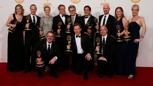 The cast and crew from Breaking Bad pose backstage with their awards for Outstanding Drama Series.