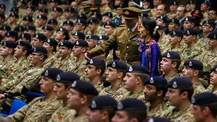 The Burmese opposition leader and Camp Commandant Major General Stuart Skeates arrive to deliver a speech at Sandhurst