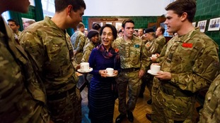 Burmese opposition leader Aung San Suu Kyi jokes with officer cadets over a cup of tea at the Royal Military Academy Sandhurst.