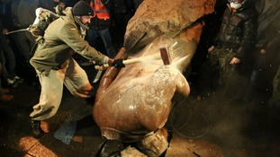 A protesters hammers a toppled statue of Lenin in Kiev