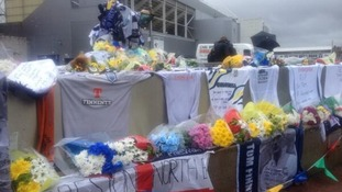 Tributes to Sir Tom Finney surround his statue.