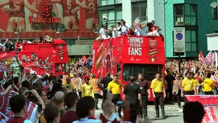 Crowds watch the bus leave the Emirates Stadium.