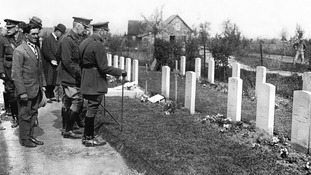 King George V visits the graves of British soldiers killed in battles at Ypres.