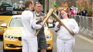 Torchbearer Michelle Smith ducking away from flame as she passes Olympic Flame to Torchbearer 085.