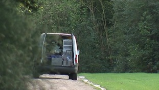 A forensics van could be seen with its back doors open.