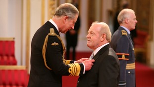 Prince Charles presents Cocker with his OBE.