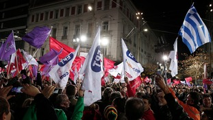 Syriza supporters wave a Greek national flag and other flags