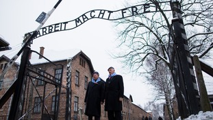 Survivors stand in front of the main gate of the former Nazi-German concentration and extermination camp KL Auschwitz I.