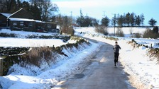 A man running through the snow near High Bradfield.