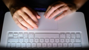 Anonymous person sitting by a laptop