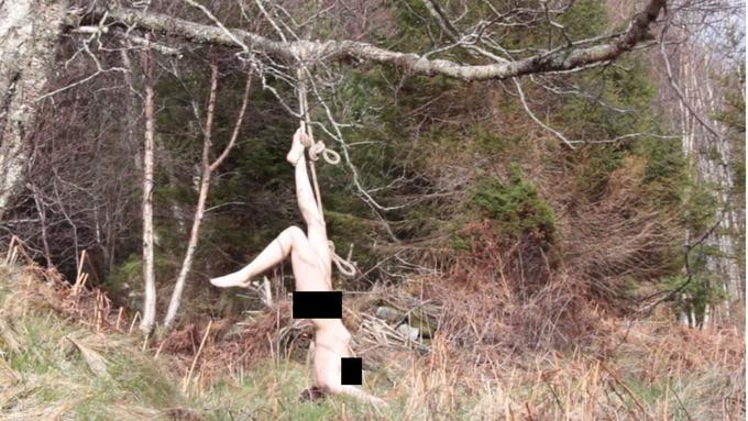 Nude women tied to trees