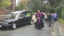 The funeral procession arrives at the church.