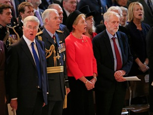 Jeremy Corbyn (right) stands silent as others, including Defence Secretary Michael Fallon (left), sing God Save the Queen.