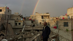 A double rainbow forms over the ruins of peoples' homes