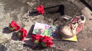 A child's shoe is surrounded by flowers at the crash site.