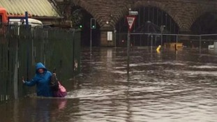 A woman is waist deep in water in Calderdale, West Yorkshire