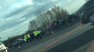 The protesters pictured with police on the side of the motorway