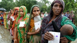Bangladeshi women wait for humanitarian aid supplies