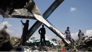 Nepalese police inspect the wreckage of a Sita Air airplane at the crash site near Katmandu, Nepal,